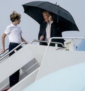Donald Trump hogs umbrella, leaves family exposed to elements on wet, frigid tarmac